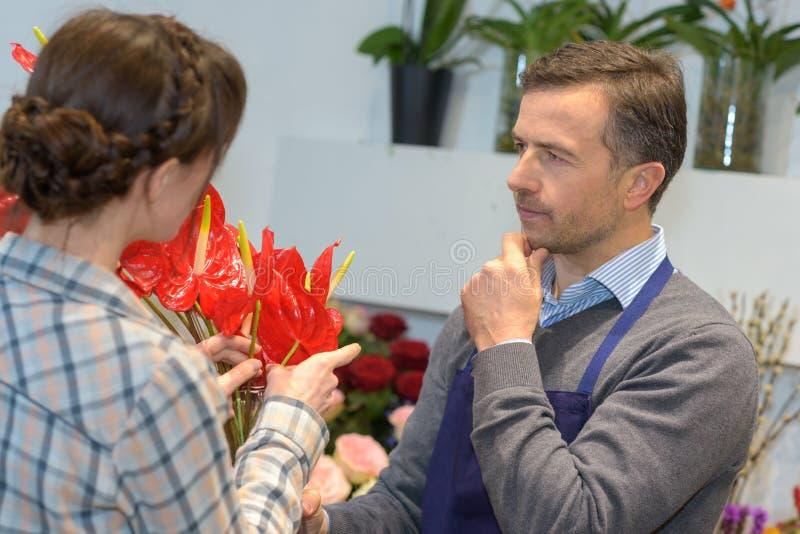 Männlicher Florist in der Betrachtung stockfoto