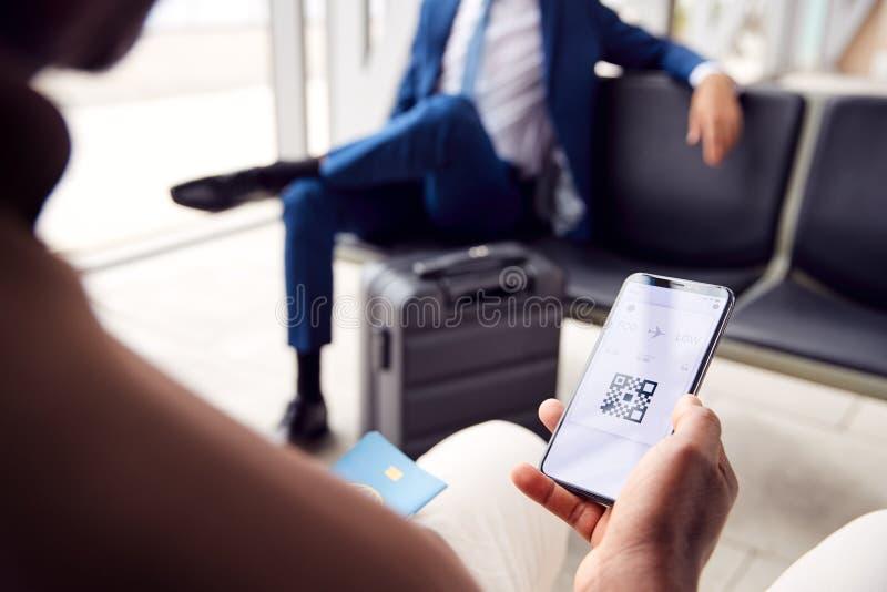 Männlicher Fluggast in Airport Departement Lounge Blick auf digitale Bordkarte auf Smart Phone stockfoto
