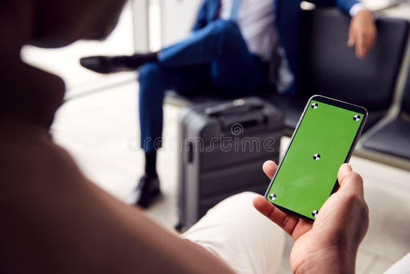 Männlicher Fluggast in der Abfluglounge des Flughafens mit Blick auf den grünen Bildschirm auf dem Smartphone lizenzfreie stockfotografie