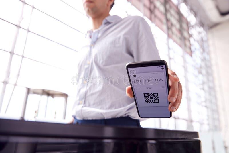 Männlicher Fluggast in der Abfluglounge, der digitale Bordkarte auf dem Smartphone scannt stockfoto