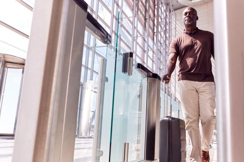 Männlicher Fluggast in der Abfluglounge Radkoffer durch Sicherheitsbarriere lizenzfreies stockfoto