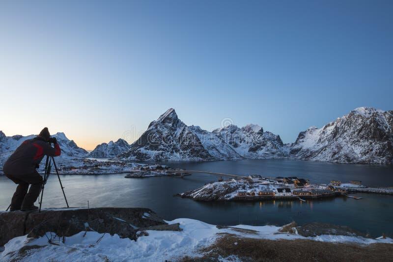 Männlicher Fotograf nimmt eine Dämmerungslandschaft beim Sakrisøy gefangen stockfotografie