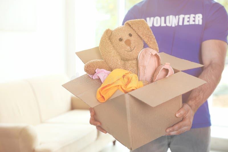 Männlicher freiwilliger haltener Kasten mit Spenden Raum für Text stockfoto