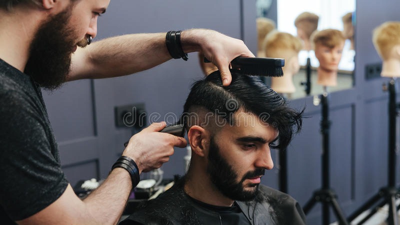 Männlicher Friseur, der Haar eines männlichen Kunden kämmt und rasiert stockfotos