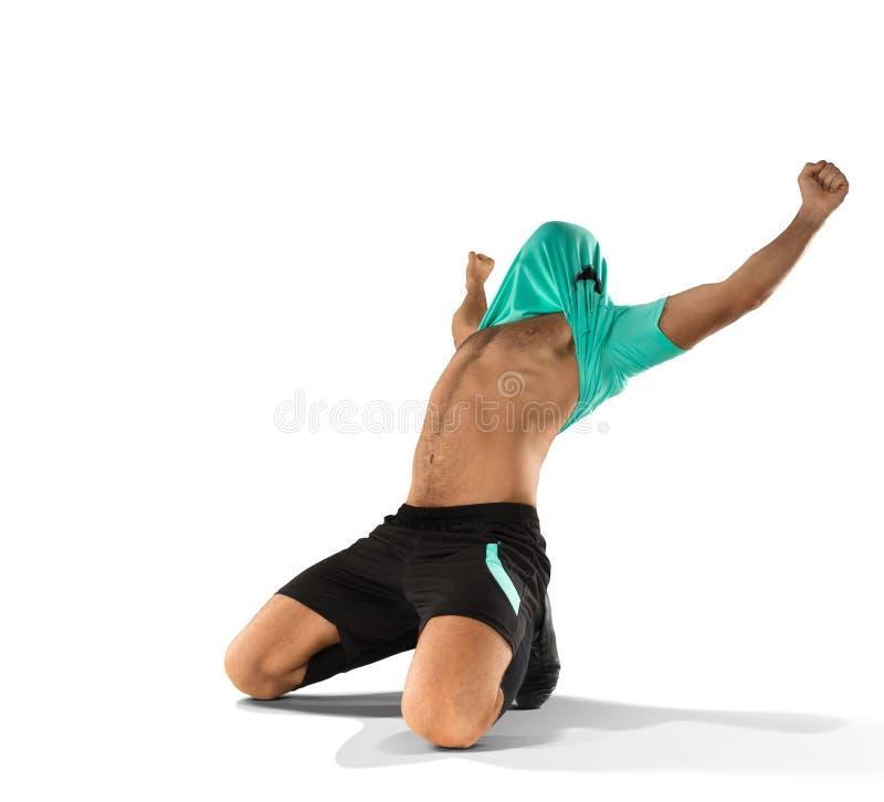 Männlicher Fußballspieler, der das Ziel lokalisiert auf Weiß feiert stockfoto