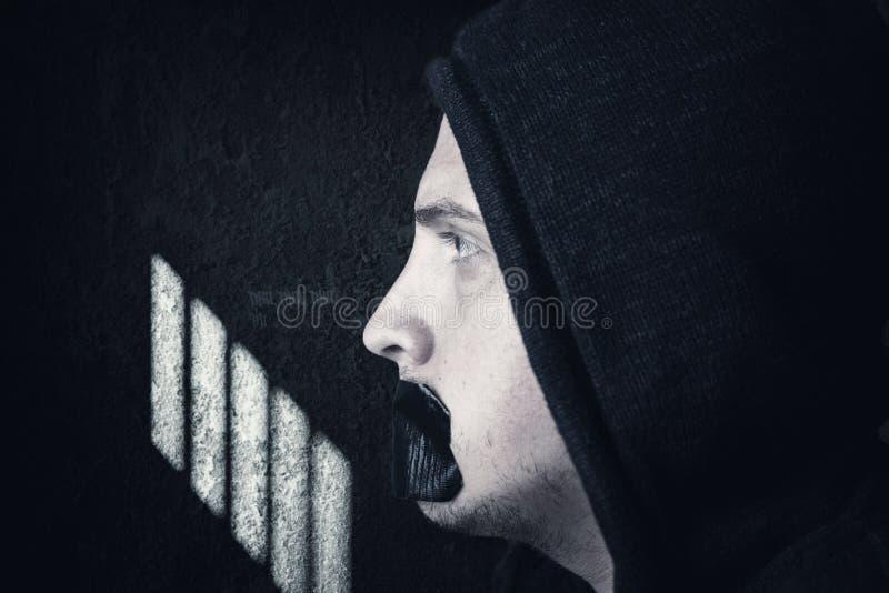 Männlicher Gefangener mit Hoodie und bedeckter Mund durch schwarzes Band stockfotos