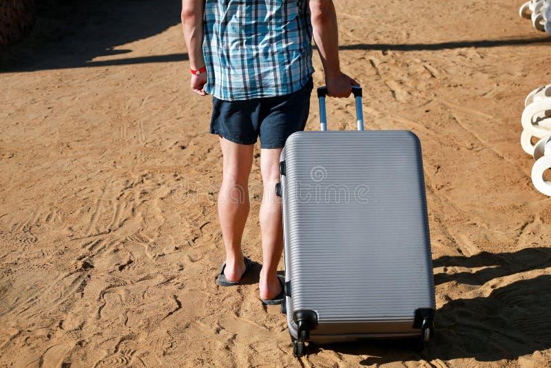 Männlicher gehender Tourist und Reisender und seinen gereisten Koffer auf sandigem Strand des Hotelerholungsortes ziehen Gut auss stockbilder