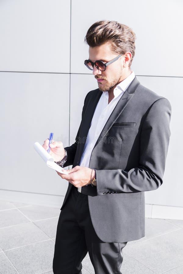 Männlicher Geschäftsmann oder Arbeitskraft im schwarzen Anzugsschreiben im Notizbuch stockfotografie