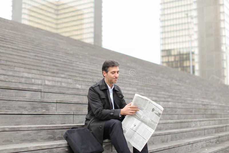 männlicher Geschäftstutor, der auf Treppe sitzt und Zeitung liest lizenzfreies stockbild