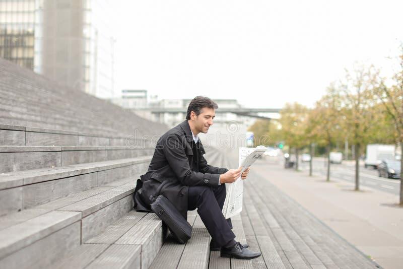 männlicher Geschäftstutor, der auf Treppe sitzt und Zeitung liest stockfotografie
