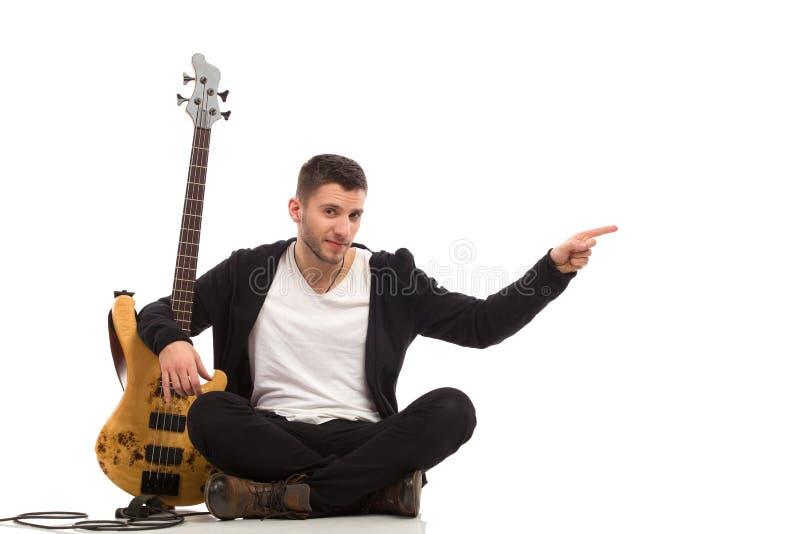 Männlicher Gitarrist, der auf dem Boden und dem Zeigen sitzt stockbilder
