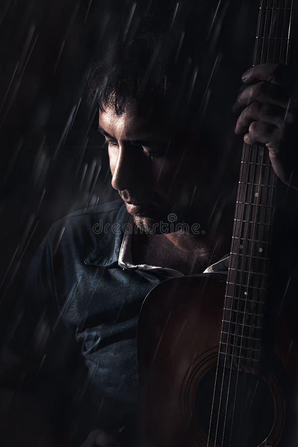Männlicher Gitarrist, der Gitarre im Regen spielt stockfoto
