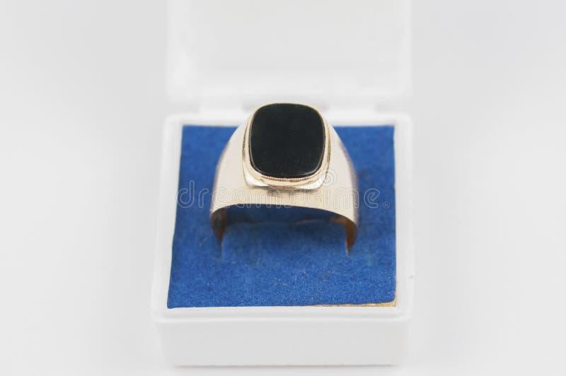 Männlicher goldener Ring mit schwarzem Stein in einem Kasten auf einem weißen Hintergrund stockbild