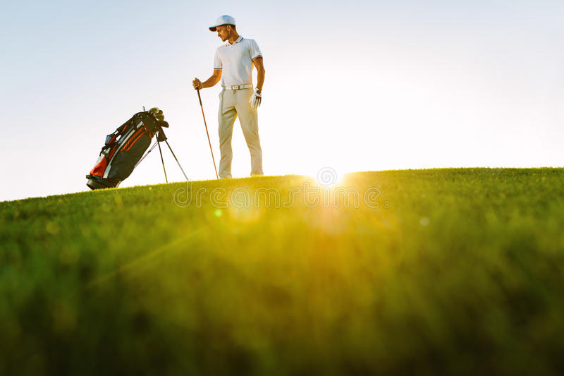 Männlicher Golfspieler, der auf Golfplatz steht stockbild
