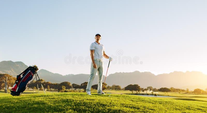 Männlicher Golfspieler, der auf Golfplatz steht stockfoto
