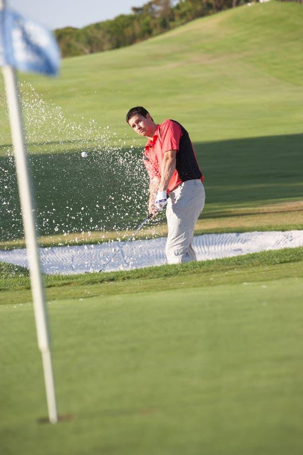 Männlicher Golfspieler, der Bunker-Schuß spielt lizenzfreies stockbild