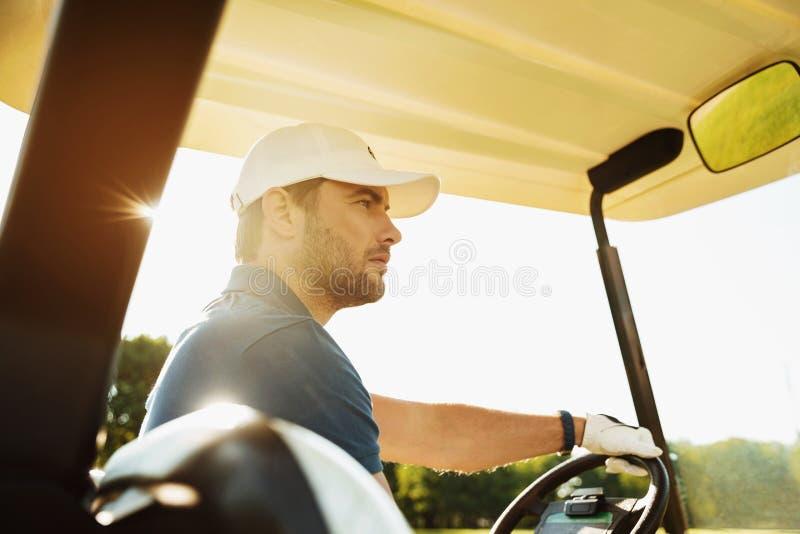 Männlicher Golfspieler, der ein Golfmobil fährt lizenzfreie stockbilder