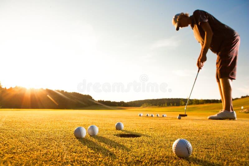 Männlicher Golfspieler, der einen Nennwert während des Sonnenuntergangs übt stockbild