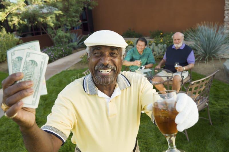 Männlicher Golfspieler, der Geld und Getränk hält lizenzfreies stockbild