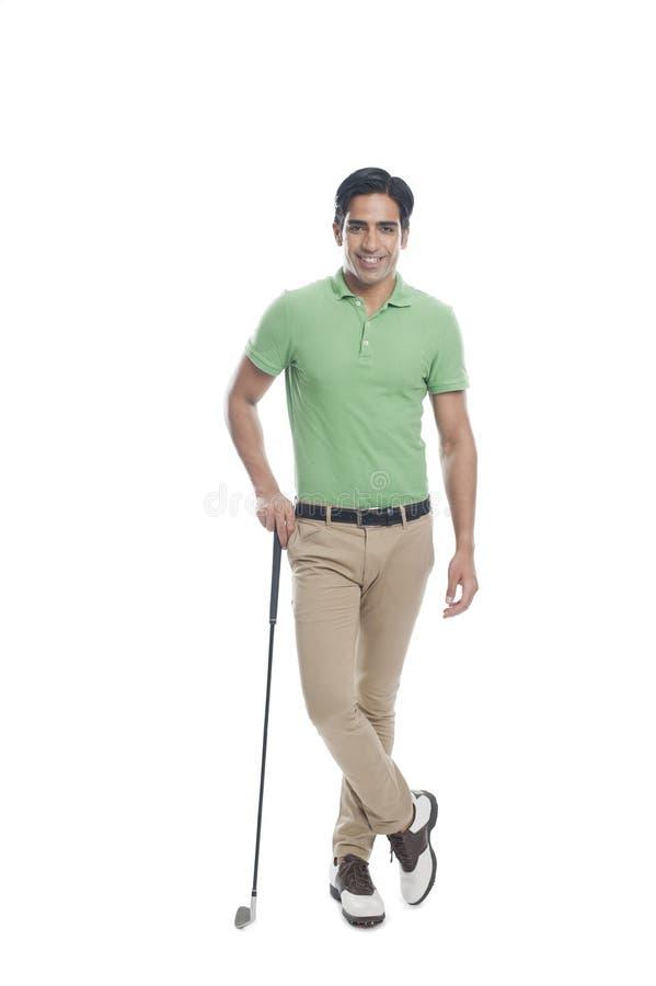 Männlicher Golfspieler, der mit einem Golfclub und einem Lächeln steht lizenzfreie stockbilder
