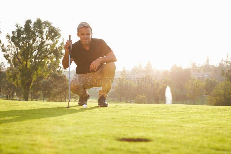 Männlicher Golfspieler, der Schlag auf Grün ausrichtet stockfoto