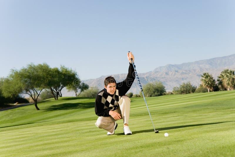 Männlicher Golfspieler, der Schlag ausrichtet stockfotografie