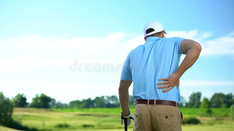 Männlicher Golfspieler spürt starke Rückenschmerzen nach Ball-Treten, Trauma stockbilder