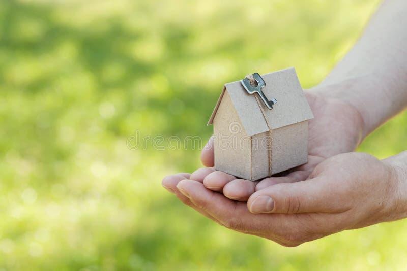 Männlicher Handgriff des Papphauses gegen grünes bokeh Gebäude, Darlehen, Einzugsfeier, Versicherung, Immobilien oder neues Haus  stockfoto