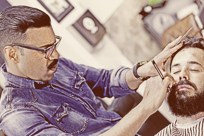 Männlicher Herrenfriseur auf einem Bart, der Sitzung rasiert stockfoto