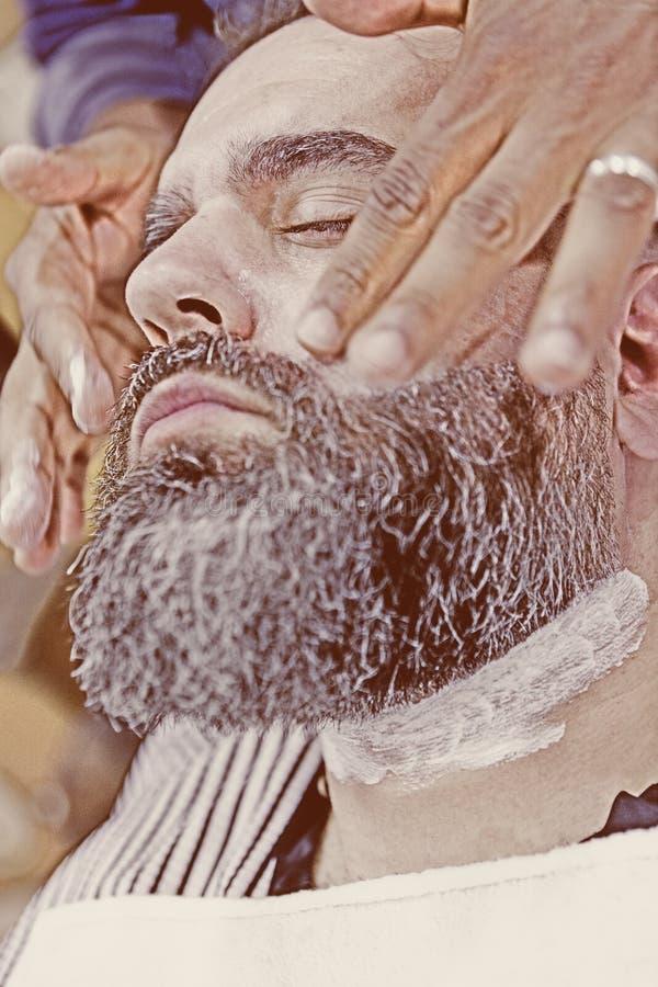 Männlicher Herrenfriseur, der einen Bart massiert lizenzfreie stockfotografie