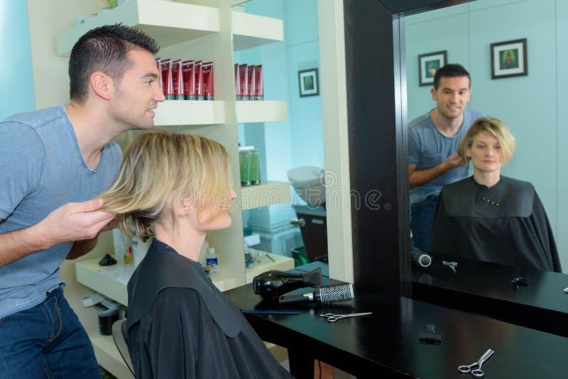Männlicher Herrenfriseur, der Haarschnitt für glückliche Frau macht stockfoto