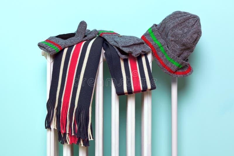 Männlicher Hutschal und -handschuhe, die auf einem Kühler trocknen stockfoto