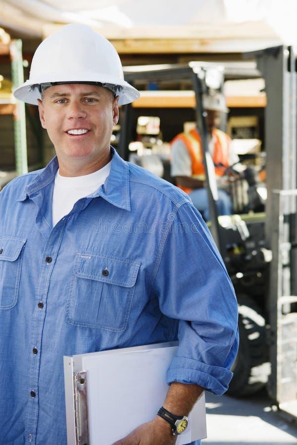 Männlicher Industriearbeiter, der Klemmbrett hält stockfotos
