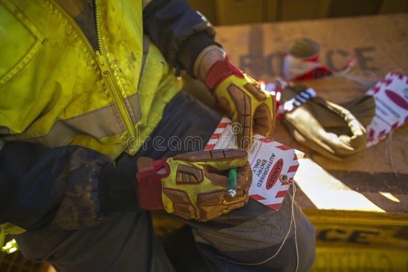 Männlicher Industriebauarbeitskraft Rigger, der Detailinformationen über roten und weißen Gefahrenumbau sich krümmt lizenzfreies stockbild