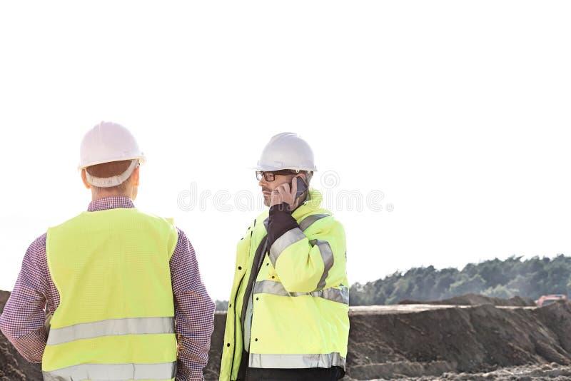Männlicher Ingenieur, der Handy bei der Stellung mit Kollegen an der Baustelle gegen klaren Himmel verwendet stockbilder
