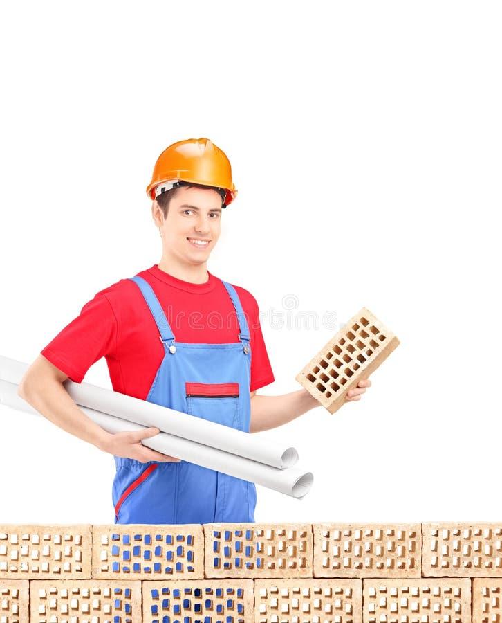 Männlicher Ingenieur mit dem Sturzhelm, der hinten einen Ziegelstein und Pläne hält stockbilder