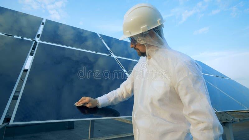 Männlicher Ingenieur säubert Sonnenkollektor stockfotos