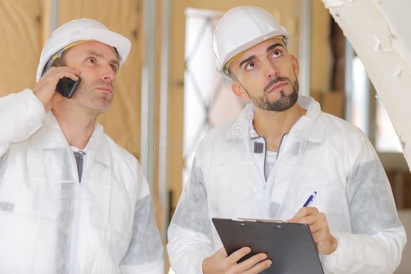 Männlicher Ingenieur und Arbeitskraft, die Innenhochbaustandort überprüft stockfoto