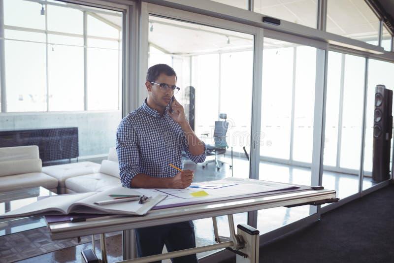 Männlicher Innenarchitekt, der auf Mobile im Büro spricht lizenzfreie stockfotografie