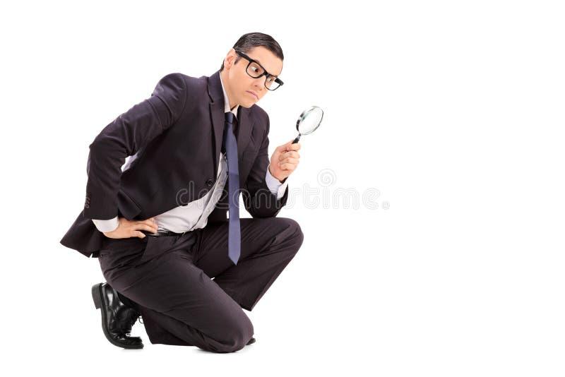 Männlicher Inspektor, der durch eine Lupe schaut stockfoto