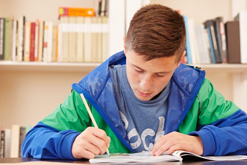 Männlicher Jugendlicher konzentriert, Hausarbeit tuend stockbild
