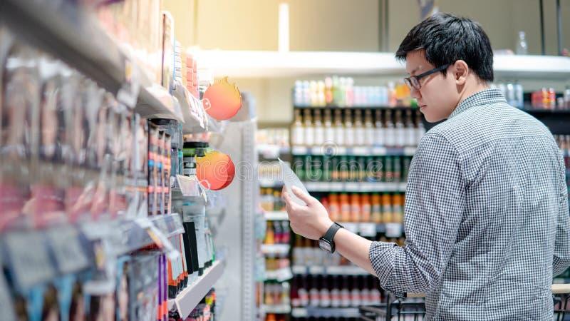 Männlicher Käufer, der Haargel im Supermarkt wählt lizenzfreies stockfoto
