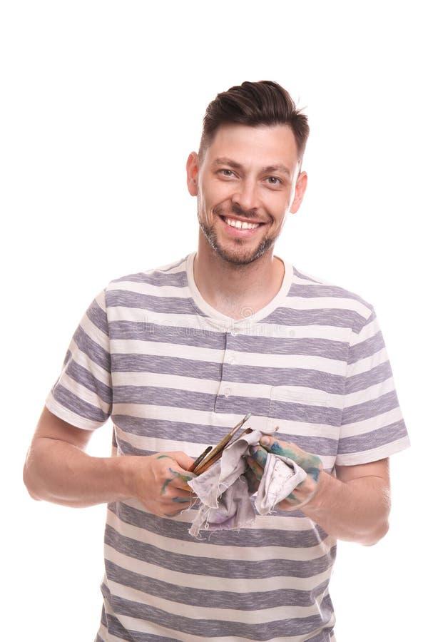 Männlicher Künstler, der seine Malerpinsel mit Lappen auf weißem Hintergrund säubert lizenzfreie stockbilder