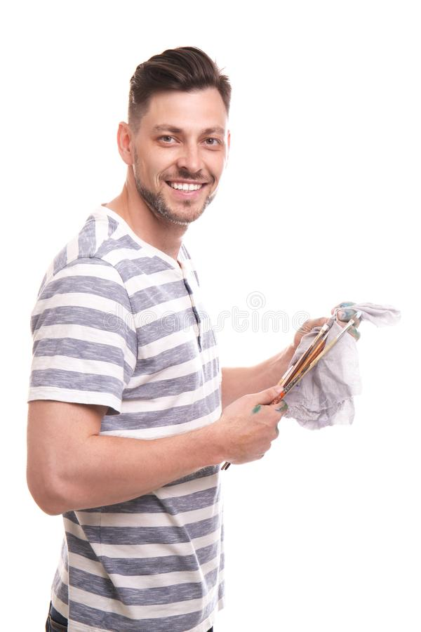 Männlicher Künstler, der seine Malerpinsel mit Lappen auf weißem Hintergrund säubert lizenzfreie stockfotos