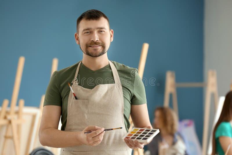 Männlicher Künstler mit Bürste und Aquarelle in der Werkstatt lizenzfreies stockfoto