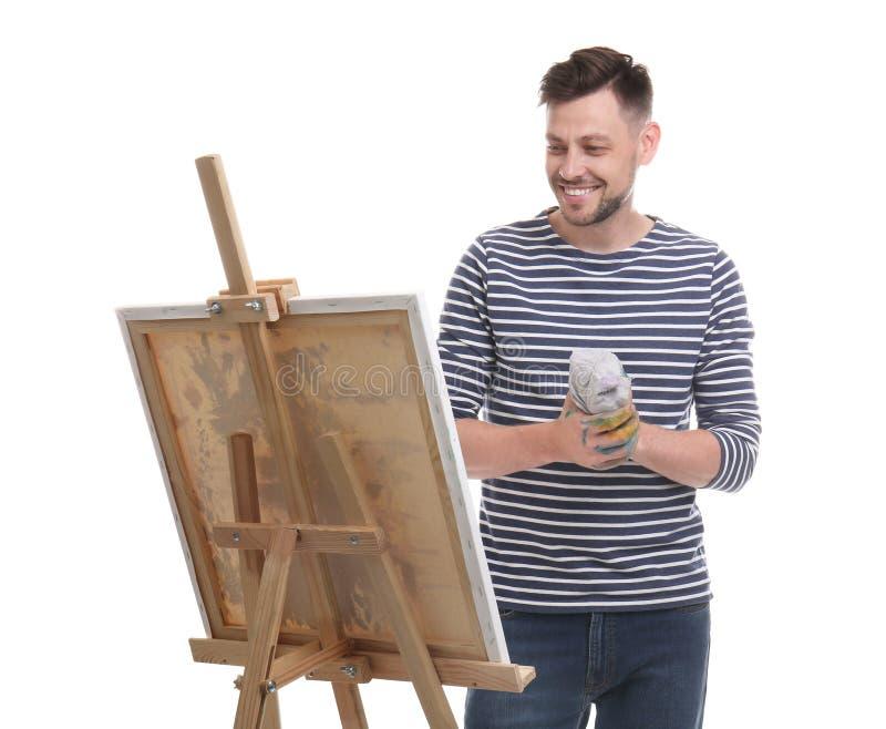 Männlicher Künstler mit Lappen nahe Gestell auf weißem Hintergrund lizenzfreie stockbilder