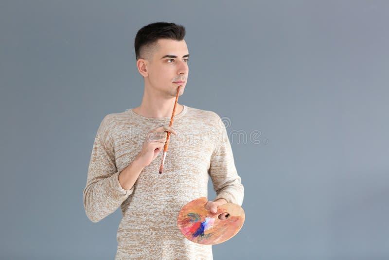 Männlicher Künstler mit Malerpinsel und Palette auf grauem Hintergrund lizenzfreie stockfotos