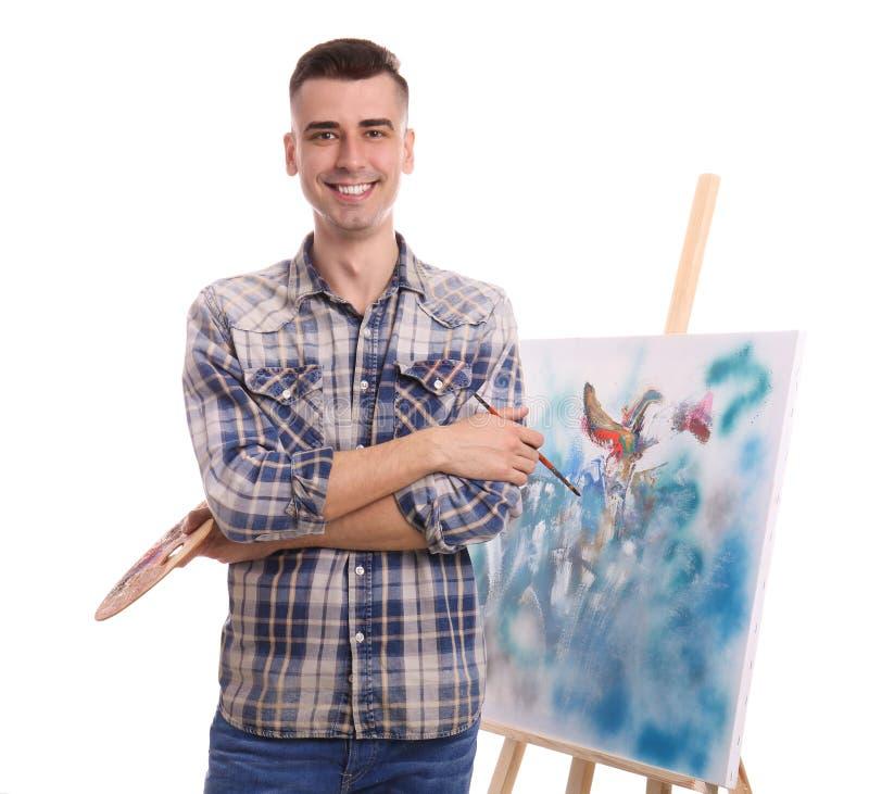 Männlicher Künstler mit Malerpinsel und Palette nahe Gestell auf weißem Hintergrund lizenzfreie stockfotos