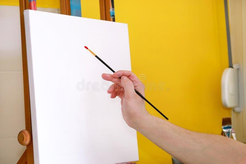 Männlicher Künstlermaler, der in der Werkstatt mit Segeltuch auf hölzernem Reißbreitgestell im Kunstfarbenstudio arbeitet Portrai stockbild