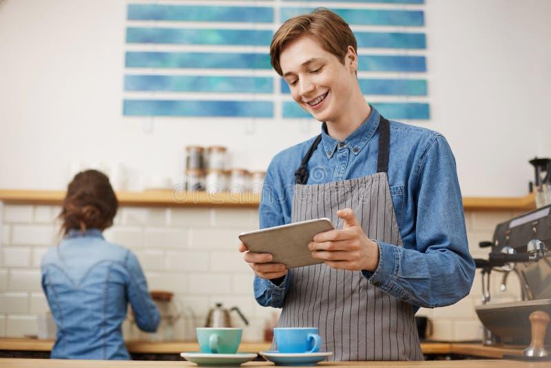 Männlicher Kassierer, der Bestellungen unter Verwendung des Vorsprunges an der hellen Kaffeestube entgegennimmt stockbilder